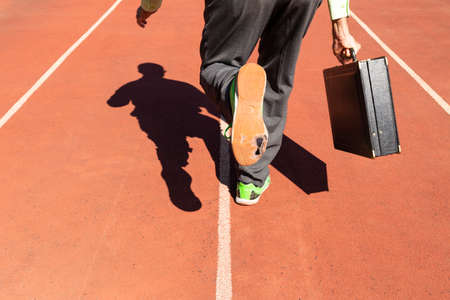 A business man in gray suit with green shirt, black briefcase and broken green sports shoes running on a running track. Reklamní fotografie