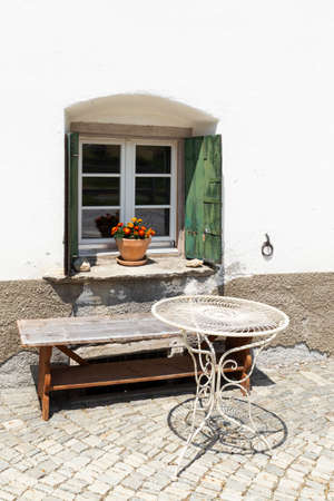 Close-up of a cozy wooden bench and a metal table in front of a window with green shutters and flowers inviting for relaxation