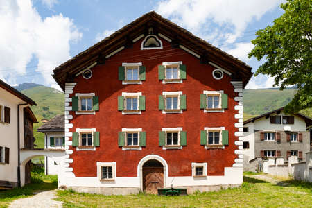 Switzerland, Nufenen. Front view of a beautiful old red painted stone house with white frames in a small town in the eastern Swiss mountains. Picture taken on 2nd of July 18