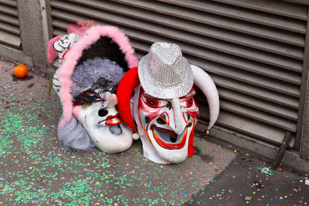 Baeumleingasse, Basel, Switzerland - March 12th, 2019. Close-up two carnival masks laying on the ground Reklamní fotografie - 124413301