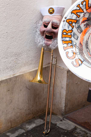 Steinenbachgaesslein, Basel, Switzerland - March 11th, 2019. Close-up of a trombone and a carnival mask