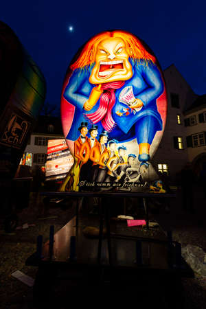 Muensterplatz, Basel, Switzerland - March 12th, 2019. A hand painted colorful illuminated carnival lantern displayed on the cathedral square Reklamní fotografie - 124413311