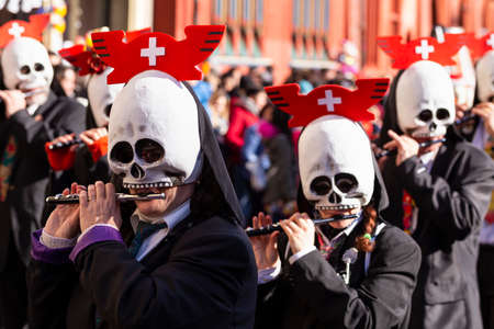 Marktplatz, Basel, Switzerland - March 13th, 2019. Portrait of carnival piccolo players wearing skull shaped masks Redakční