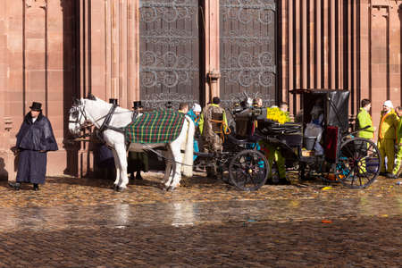 Muensterplatz, Basel, Switzerland - March 13th, 2019. A carnival horse carriage parked in front of the cathedral Redakční