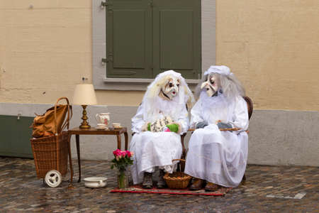 Rheinsprung, Basel, Switzerland - March 13th, 2019. Two carnival participants disguised as old ladies in white dressing gowns Editorial