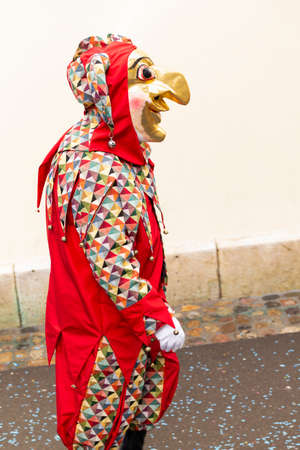 Rheinsprung, Basel, Switzerland - March 13th, 2019. Portrait of a carnival participant in red costume with gold colored mask Redakční