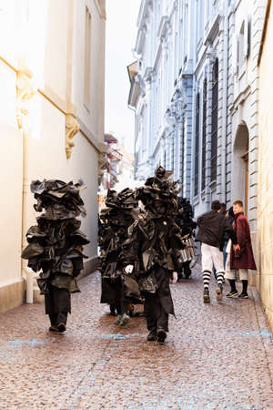 Rheinsprung, Basel, Switzerland - March 13th, 2019. Group of carnival participants in black plastic bag costumes Editorial