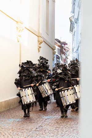 Rheinsprung, Basel, Switzerland - March 13th, 2019. Group of snare drummers in black costumes walking in the old town Reklamní fotografie - 124413326