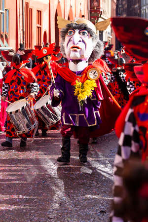 Marktplatz, Basel, Switzerland - March 13th, 2019. A drum major in purple red costume leading his group in the street Reklamní fotografie - 124413327