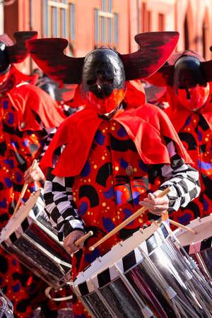 Marktplatz, Basel, Switzerland - March 13th, 2019. Portrait of a carnival snare drummer in red costume Redakční