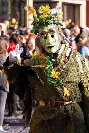 Marktplatz, Basel, Switzerland - March 13th, 2019. Portrait of a carnival participant in a green colored unique costume