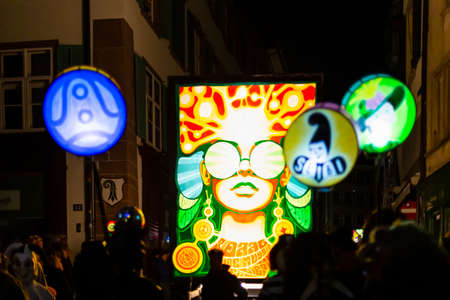 Spalenberg, Basel, Switzerland - March 11th, 2019. Close-up of a carnival group marching in the old town with their illuminated main and stick lanterns. Editorial