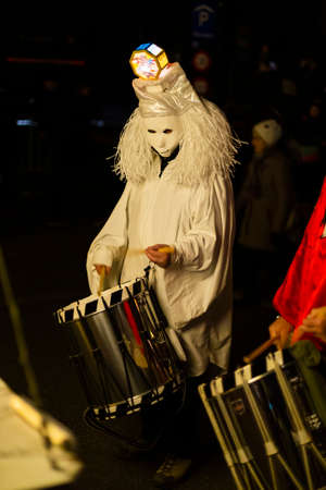 Marktgasse, Basel, Switzerland - March 11th, 2019. Single drummer in a white costume during the carnival morgestraich parade