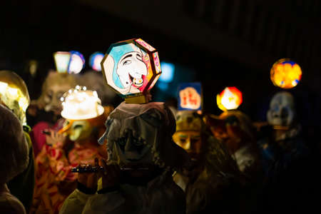 Marktgasse, Basel, Switzerland - March 11th, 2019. Close-up of piccolo players in their individual carnival costumes with illuminated head lanterns. Reklamní fotografie - 124413336