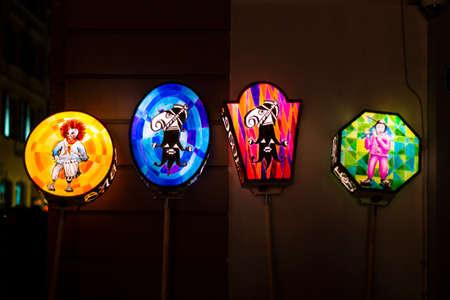 Stadthausgasse, Basel, Switzerland - March 11th, 2019. Close-up of four colorful illuminated carnival pole lanterns.