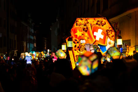 Schneidergasse, Basel, Switzerland - March 11th, 2019. Close-up of a carnival group marching in the old town with their illuminated main and head lanterns. Editorial