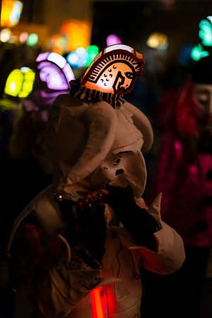 Schneidergasse, Basel, Switzerland - March 11th, 2019. Close-up of a piccolo player in his individual carnival costume with illuminated head lantern. Reklamní fotografie - 124413342