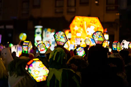 Ruemelinsplatz, Basel, Switzerland - March 11th, 2019. Close-up of a carnival group marching in the old town with their illuminated main and head lanterns. Reklamní fotografie - 124413344