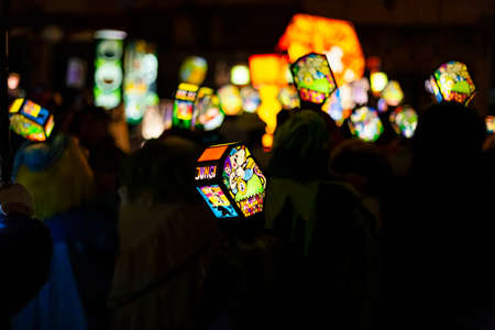 Ruemelinsplatz, Basel, Switzerland - March 11th, 2019. Close-up of a carnival group marching in the old town with their illuminated main and head lanterns.