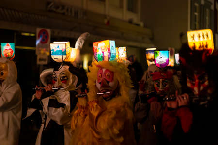 Ruemelinsplatz, Basel, Switzerland - March 11th, 2019. Close-up of piccolo players in their individual carnival costumes with illuminated head lanterns. Reklamní fotografie - 124413346