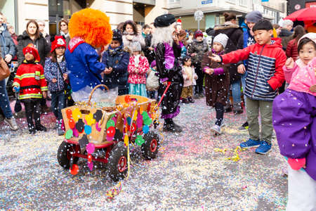 Freie Strasse, Basel, Switzerland - March 12th, 2019. A small colorful decorated carnival cart on a confetti covered street Reklamní fotografie - 124413347