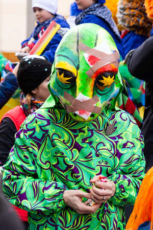 Freie Strasse, Basel, Switzerland - March 12th, 2019. Close-up of a green lizard carnival costume and mask Redakční