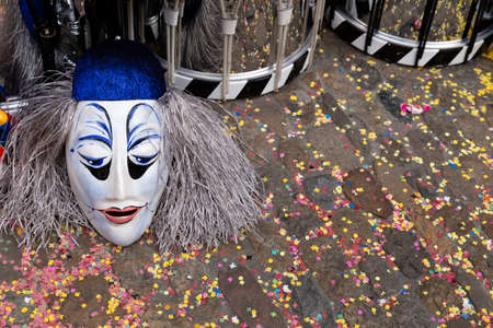 Augustinergasse, Basel, Switzerland - March 12th, 2019. Close-up of a carnival mask and snare drums on a confetti covered street Redakční