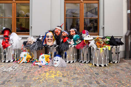 Augustinergasse, Basel, Switzerland - March 12th, 2019. Carnival masks and snare drums piled up in a street corner Reklamní fotografie - 124413352