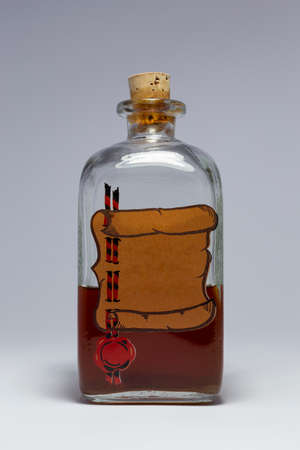 A vintage medicine bottle with cork filled with orange liquid and furnished with an empty label designed like a parchment roll with red sealing wax. Arrangement on white background.