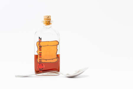A vintage medicine bottle with cork filled with orange liquid and furnished with an empty label designed like a parchment roll with red sealing wax and a silver spoon on white background