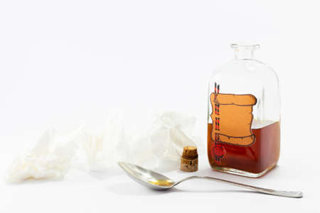 Arrangement of a spoon, handkerchiefs and a vintage medicine bottle with cork filled with orange liquid and furnished with an empty label designed like a parchment roll with red sealing wax on white background Reklamní fotografie - 124437819
