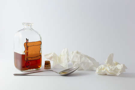 Arrangement of a spoon, handkerchiefs and a vintage medicine bottle with cork filled with orange liquid and furnished with an empty label designed like a parchment roll with red sealing wax on white background Stock Photo