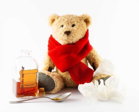 A sick teddy bear with red scarf, a spoon, creased handkerchiefs and a vintage medicine bottle with cork and furnished with an empty label designed like a parchment roll with sealing wax on white background