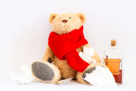 A sick teddy bear with red scarf, a spoon, creased handkerchiefs and a vintage medicine bottle with cork and furnished with an empty label designed like a parchment roll with sealing wax on white background Reklamní fotografie - 124437848