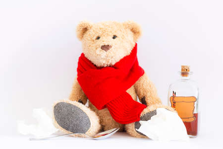 A sick teddy bear with red scarf, a spoon, creased handkerchiefs and a vintage medicine bottle with cork and furnished with an empty label designed like a parchment roll with sealing wax on white background Reklamní fotografie - 124437860