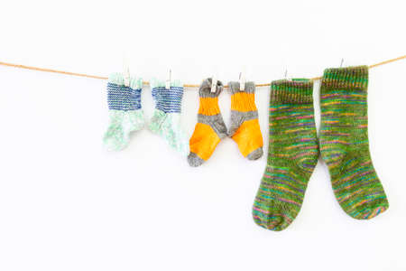 Several pairs of colorful woolen socks of various sizes hanging on a rope with white background