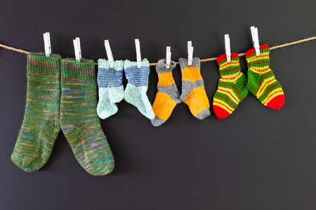 Several pairs of colorful woolen socks of various sizes hanging on a rope with red background Reklamní fotografie - 124437826