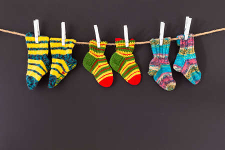 Several pairs of colorful woolen socks of various sizes hanging on a rope with red background