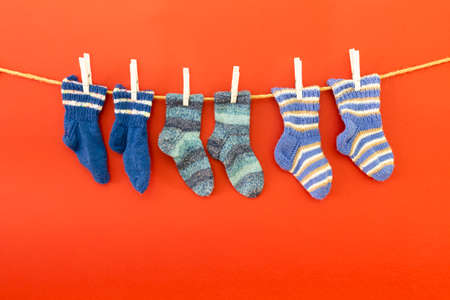 Several pairs of colorful woolen socks of various sizes hanging on a rope with white background Reklamní fotografie - 124437966