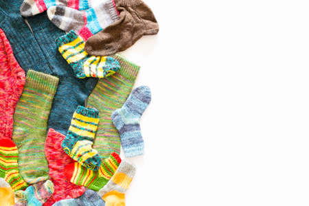 Top view of an assortment of colorful woolen socks of various sizes on white background Reklamní fotografie - 124437969