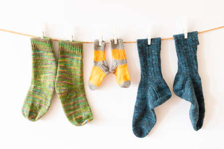 Several pairs of colorful woolen socks of various sizes hanging on a rope with white background Reklamní fotografie - 124437978