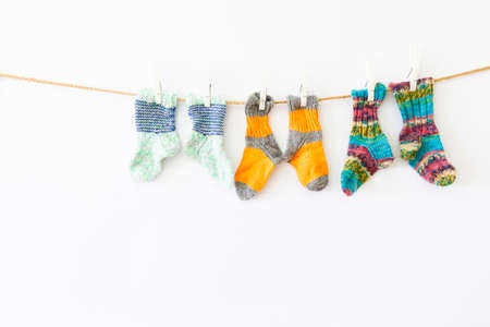 Several pairs of colorful woolen socks of various sizes hanging on a rope with white background Reklamní fotografie - 124437981