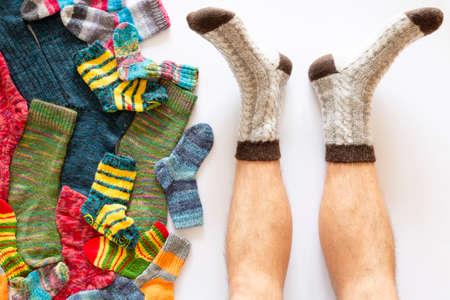 Top view of an assortment of colorful woolen socks of various sizes on white background with a pair of feet wearing gray brown socks Reklamní fotografie - 124437984