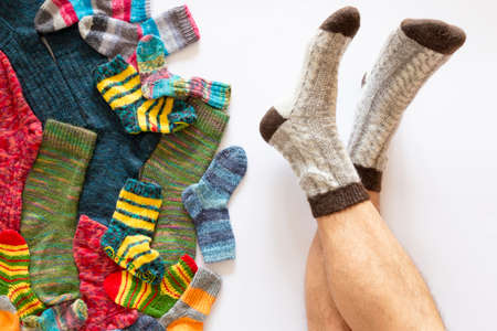 Top view of an assortment of colorful woolen socks of various sizes on white background with a pair of feet wearing gray brown socks