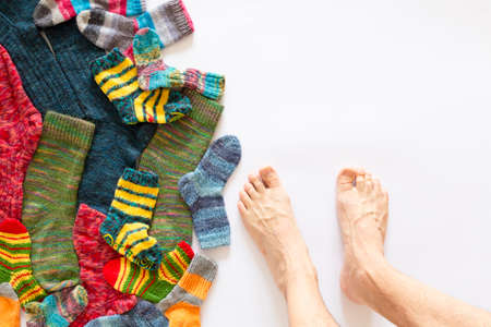 Top view of an assortment of colorful woolen socks of various sizes on white background with a pair of naked feet Stock Photo