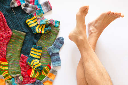Top view of an assortment of colorful woolen socks of various sizes on white background with a pair of naked feet Reklamní fotografie - 124438029