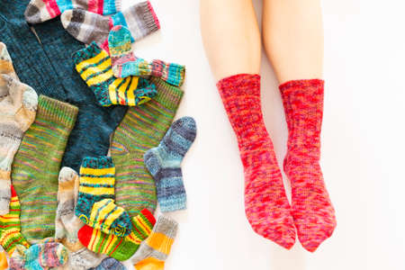 Top view of an assortment of colorful woolen socks of various sizes on white background with a pair of feet wearing red socks Stock Photo