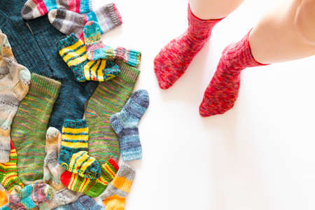 Top view of an assortment of colorful woolen socks of various sizes on white background with a pair of feet wearing red socks Reklamní fotografie