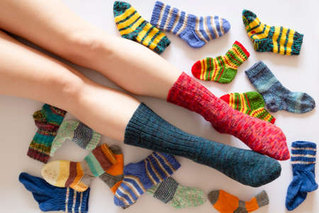 Top view of an assortment of colorful woolen socks of various sizes on white background with a pair of feet wearing a red and a blue sock