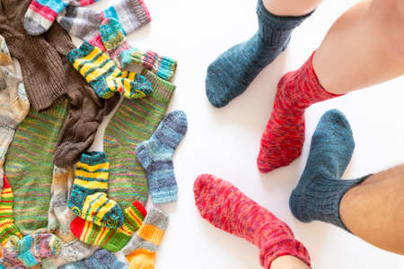 Top view of an assortment of colorful woolen socks of various sizes on white background with two pairs of feet wearing a red and a blue sock Reklamní fotografie - 124438071